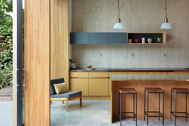 The kitchen's minimal scheme allows the custom-made joinery, including the brass-clad island bench-top, to take centre stage.
