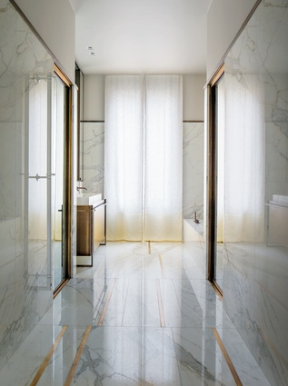 The bathroom appears luxurious with the floor-to-ceiling marble and brass veins and bespoke cabinetry.