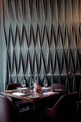 The diamond-shaped design of the restaurant's bespoke curtain reflects the geometric forms of the restaurant bottle display, a garden trellis and arbour.