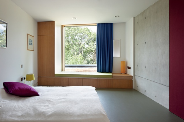 The guest bedroom features a window seat that overlooks the garden.