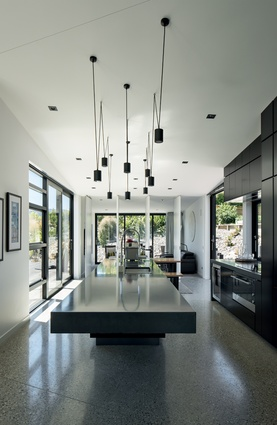 The kitchen lighting was custom-made by the architects using standard light fittings. The kitchen bench is cantilevered concrete.