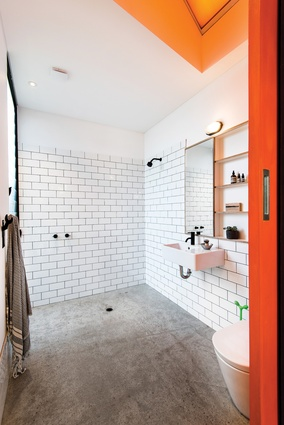 A tinted skylight floods the bathroom with a wash of orange light, the colour seen more boldly on the sliding door.