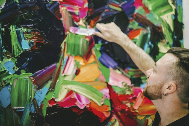 Trolove applying paint to a canvas.