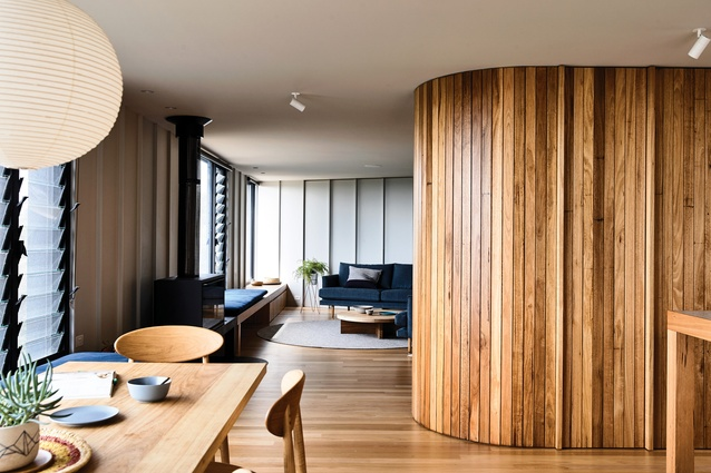 A curved timber joinery wall breaks down the open-plan living area – on one side it adds a sense of intimacy to the lounge and on the other it conceals a pantry and fridge.