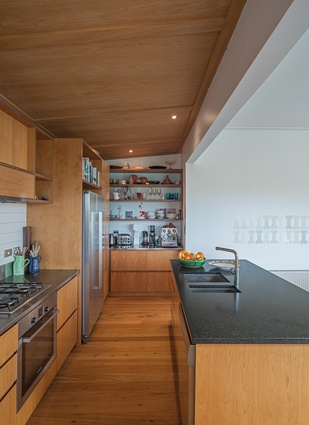The kitchen island top is black velvet granite. On the wall is an artwork by Wayne Youle.