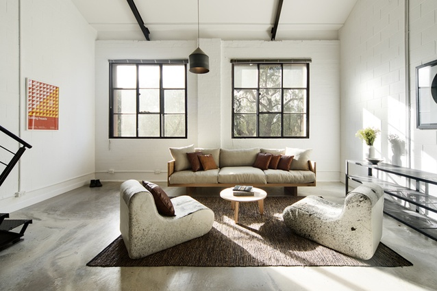 The serene living room is flooded with light, thanks to the large original windows.