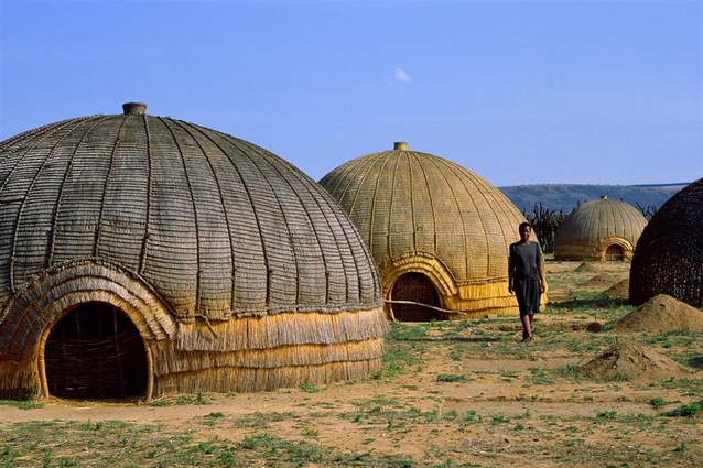 "Zulu or ""beehive"" huts, located along South Africa's eastern coast. Known as <em>iQukwane</em>, they are constructed from layers of grass covering a wooden framework, with extremely low doorways so enemies had to stoop to enter."