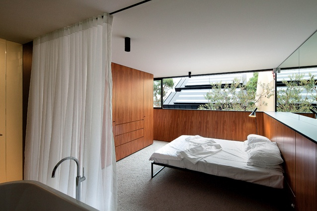 """The timber-lined master bedroom with low walls angled out to """"scoop in the sun."""""""
