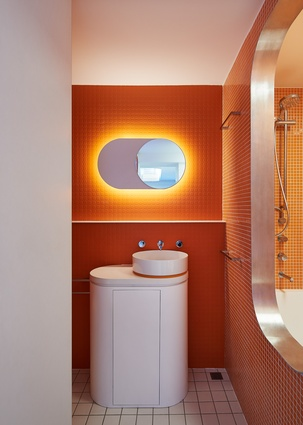 Orange accents, seen boldly in the bathroom and more subtly elsewhere, form a counterpoint to the otherwise monochromatic palette.