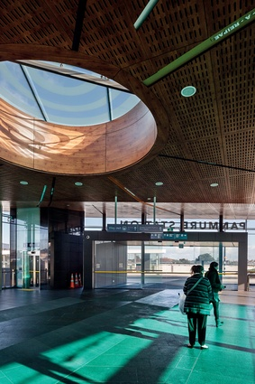 An oculus in the perforated laminate ceiling pools light in the centre of the concourse, while coloured glazing adds light and warmth to the building's interior.
