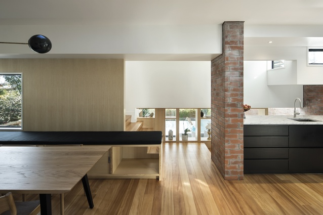 A bench seat runs beyond the dining room towards a brick wall and creates a portal to the stairway. Floors in this new part of the home are recycled kauri.