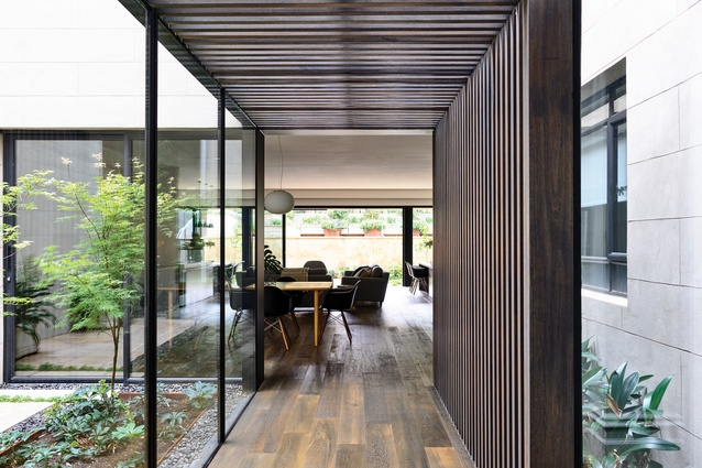 A low passage framed by dark-stained timber battens leads from the existing house to the rear extension.
