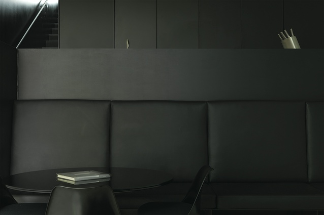 The matte-black kitchen hovers over the dining room below in Ian Moore's design.