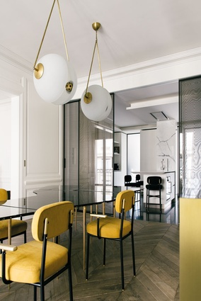 Rimadesio glass doors separate the dining room from the kitchen, while Dualita seating from david/nicolas feature in both areas.