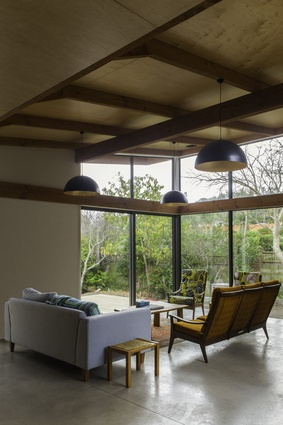 Lounge area of Pitoitoi House in Days Bay, Wellington. Exposed timber trusses allow for an elegant and cost-effective roof system.