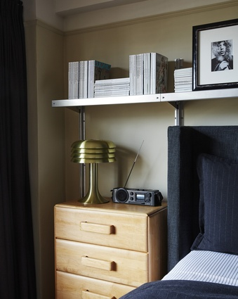 Wherever possible, storage and display space is provided, such as the industrial E-Z Shelving System above the bed.