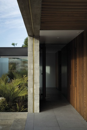 At the entrance, large-format Italian porcelain tiles from SCE and a cedar screen wall lead visitors to the front door.