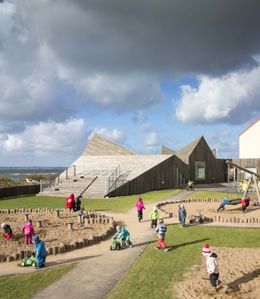 Råå Day Care Center in Sweden by Dorte Mandrup Arkitekter. The building's design is based on the surrounding dunes and the complex features a large playground.