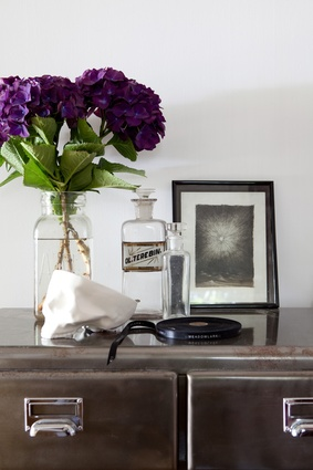Vintage finds such as the filing cabinet and old apothecary bottles bring an elegant retro feel to the home.