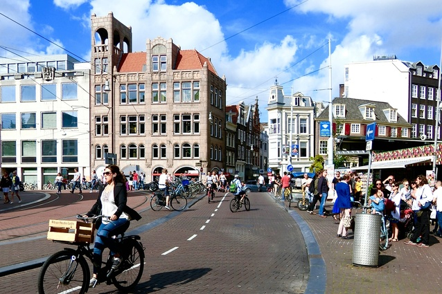 Pedal power in Amsterdam: dedicated cycleways encourage people to choose physical activity instead of opting for private cars, leading to greater health benefits and less pollution.