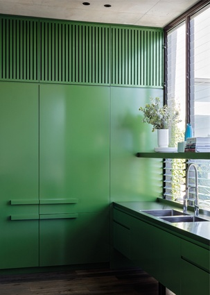 The kitchen's glossy bright-green cabinetry visually connects it to the garden.