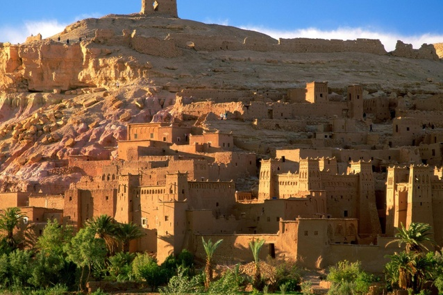 Aït Benhaddou in southern Morocco is an example of an <em>ighrem</em> (fortified village). The village consists of a range of crowded earthern clay dwellings surrounded by high defensive walls, reinforced by angle towers.