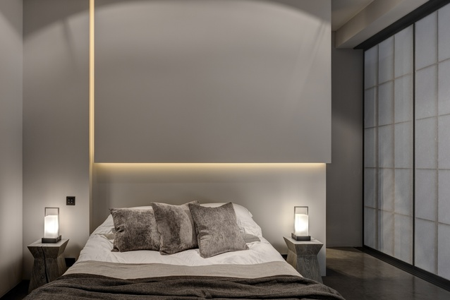 In the bedroom, a sculptural vertical bulkhead above the bed conceals subtle illumination in narrow slots.