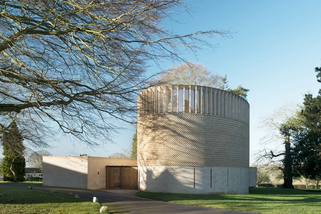 Bishop Edward King Chapel by Niall McLaughlin Architects. A circular building with a textured stone exterior topped by a wooden roof with clerestory windows that let light in.