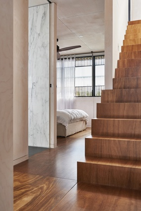 The bedrooms are pragmatically planned and finished in plywood panelling, while crafted stairs lead to the roof.