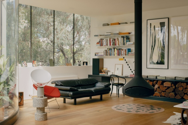 A black suspended wood heater visually anchors the living areas.