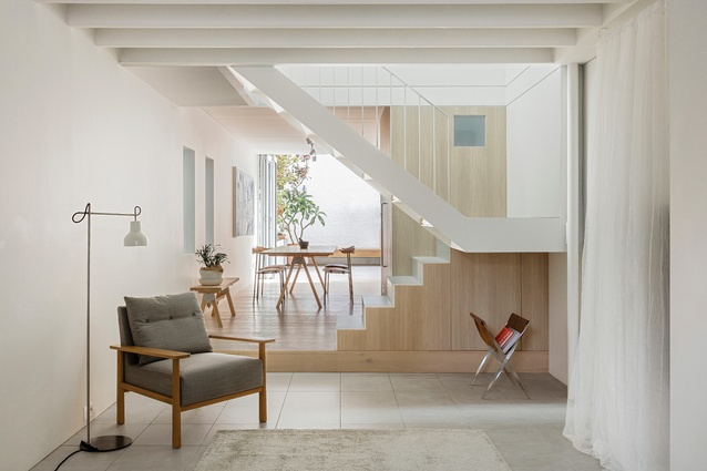 Daylight streams down from the new part of the house to the old through a centrally located white steel staircase.