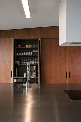 Full-height plywood cabinetry lends visual warmth to the streamlined kitchen.