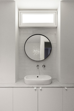 The lack of windows in the bathroom is countered with glossy tiles and mirrors that bounce light and an opaque light box.