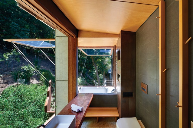 In the ensuite, a floor-to-ceiling retractable window opens the western wall to the bush.