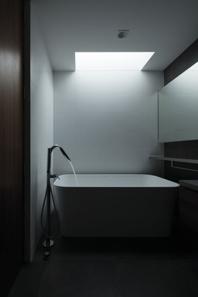 Light streams into the bathroom from above, illuminating a Victoria & Albert Edge free-standing bath.