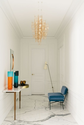 The entry is memorable for its few key pieces of furniture, including lighting by Dandelight by Studio Drift.