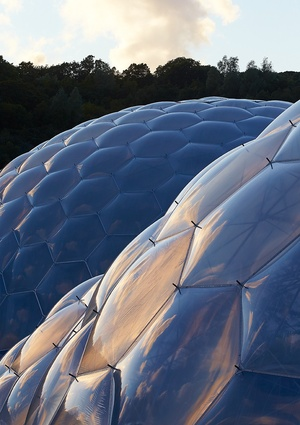 Eden Project, built in 2001. The lightweight ETFE panels naturally adapt to the local topography. The biomes were partially inspired by Buckminster Fuller's geodesic designs.