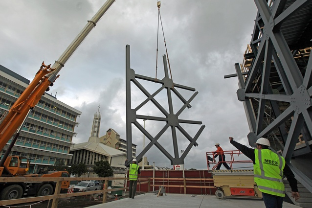 Structural steel components are craned into position.