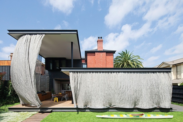 A two-storey-high sheet of fine stainless steel mesh fabric slides across to protect the living areas from the harsh western sun.