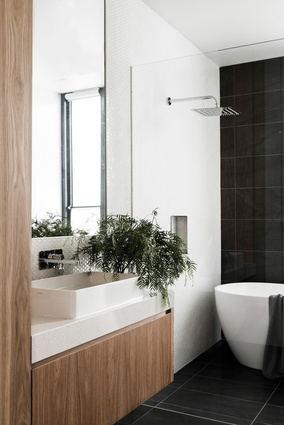 The restrained palette of timber and clean, white surfaces continues into the bathroom.