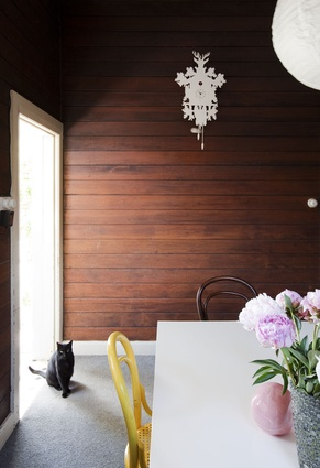 A funky cuckoo clock in the dining room adds interest to traditional timber-lined walls.
