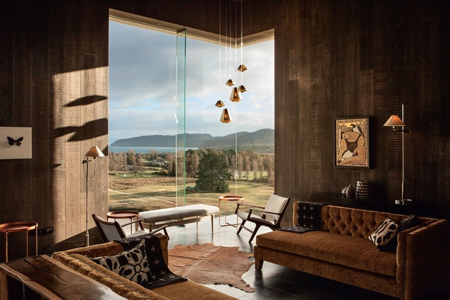 The bar is lined in a dark-stained cedar, giving a moody feel. In this room, floor-to-ceiling windows give views over the lake.