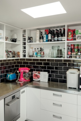 The scullery features open shelves for storage of cooking ingredients, pots, pans and large appliances.