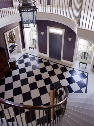 The foyer of the Melbourne Stately home features a modern take on the classic checkerboard floor and an elegant curved staircase.