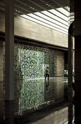 A work by Sara Hughes called Orangery has been applied to both sides of a glass wall which veils a firewall and the perimeter of the building next door.