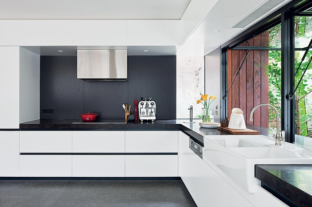 The kitchen is sleek and modern and can be opened to the outdoors.