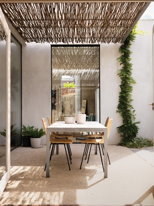 A pergola of reclaimed tea-tree sticks filters sunlight to create a play of shadows.