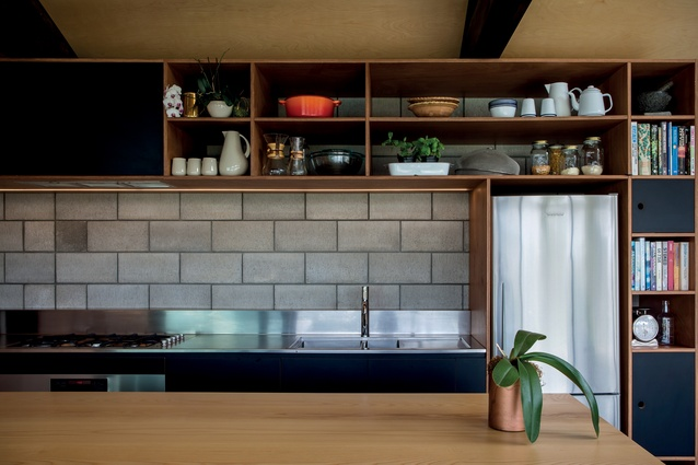Bespoke timber cabinetry contrasts the breeze-block concrete wall.